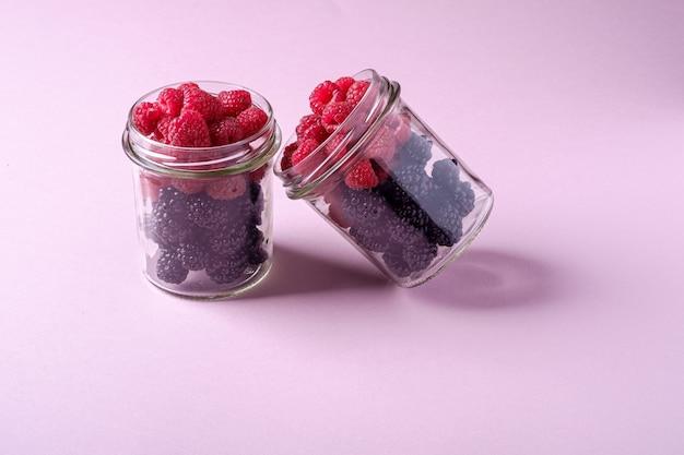 ピンクの紙の上の2つのガラスの瓶にラズベリーとブラックベリーの甘い有機ジューシーなベリー