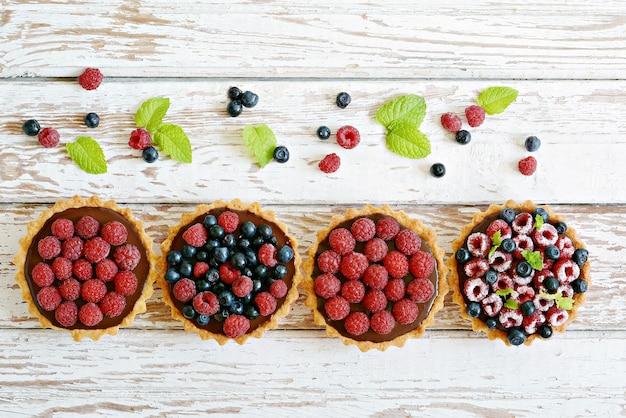Тарталетки из малины и черники с шоколадным ганашем, свежими ягодами и листьями мяты, выборочный фокус.
