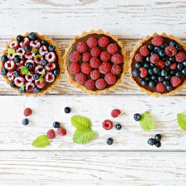 ラズベリーとブルーベリーのタルト、チョコレートガナッシュ、フレッシュベリー、ミントの葉、セレクティブフォーカス。