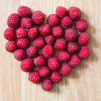 Raspberry berries heart symbol on wooden texture