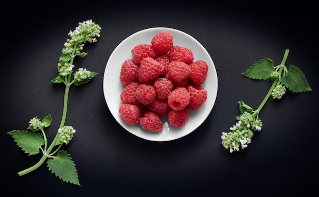 白い受け皿とメリッサの小枝にラズベリーの果実