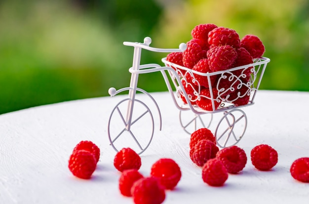 Raspberry berries on a white wooden background.