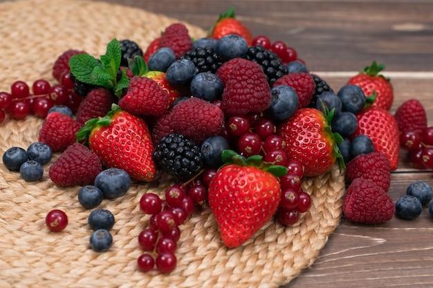 Малина ежевика и черника фон на деревянный стол свежие ягоды