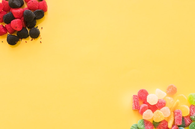 Raspberry and blackberry flavored and shaped jelly candies on the corner of yellow background