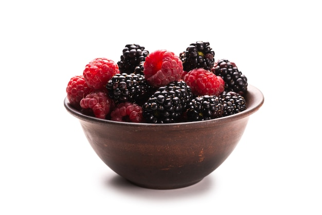 Raspberry blackberry and mint leaf in ceramic brown bowl isolated on white
