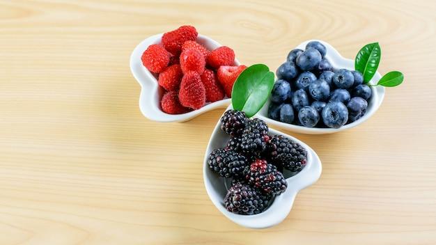 木製のテーブルのプレートにラズベリー、ブルーベリー、ブラックベリー。フルーツバランスの取れた食事、健康的な食事。