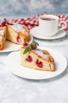 Raspberry cake with powdered sugar and fresh raspberries on a light . summer berry dessert.
