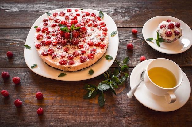 木製のテーブルに緑茶とラズベリーケーキ