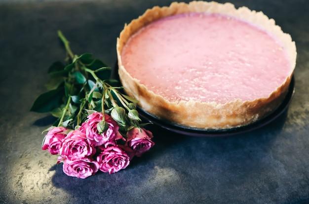 장미 꽃과 함께 라즈베리 치즈 케이크입니다. 발렌타인 데이나 어버이날을 위한 맛있는 선물. 부엌에 아름다운 평면이 놓여 있습니다. 수제 디저트에 핑크 색상입니다.