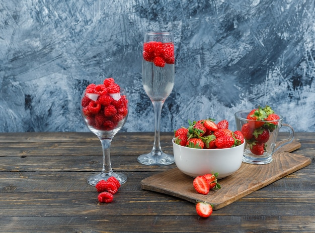 Raspberry in crystal glass and strawberries in a bowl