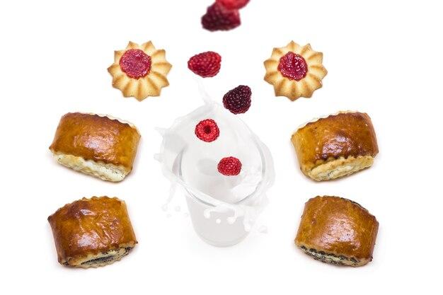 Малина попадает в стакан с молоком с брызгами, вокруг которых идет вкусное печенье