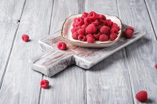 Плоды малины в тарелке на старой разделочной доске, здоровая куча летних ягод на серой деревянной доске, угловой вид