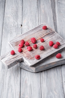 Raspberry fruits on old cutting board, healthy pile of summer berries on grey wooden table, angle view