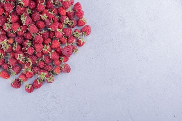 Куча малины разбросана на мраморном фоне. фото высокого качества