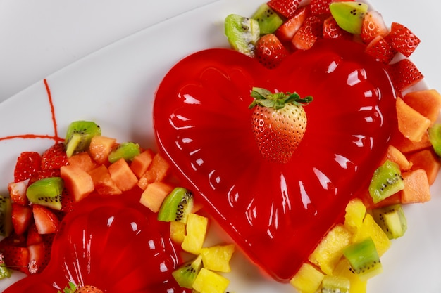 Raspberry heart gelatin decorated with chopped fruit on white plate