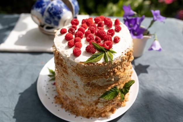 Малиновый домашний торт на столе в саду солнечным летним утром