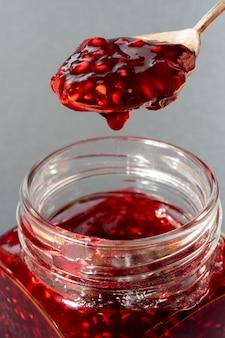 Raspberry jam in a glass jar. spoon with jam.