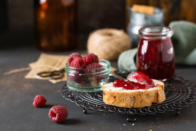 ガラスの瓶にラズベリー ジャムと古いレトロな背景に新鮮なラズベリーの果実のサンドイッチ
