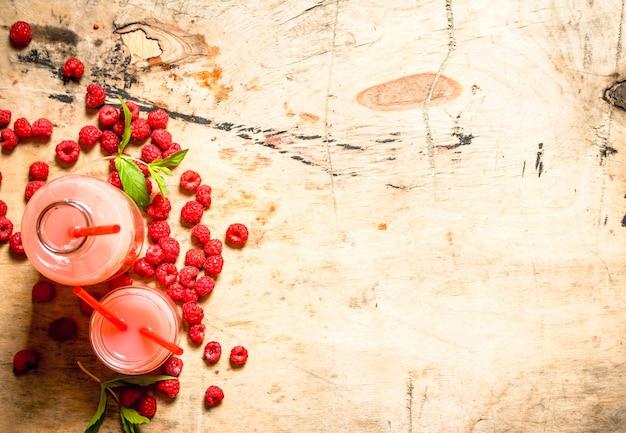 ピッチャーとグラスにラズベリージュース。木製のテーブルの上。