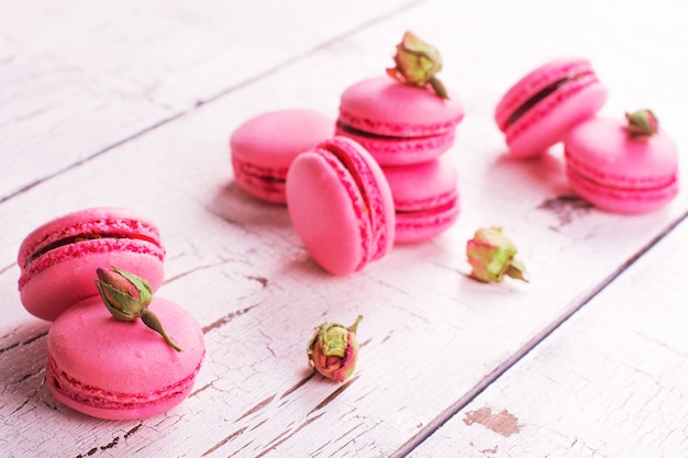 Raspberry macaroons and dry roses buds on white wooden background.