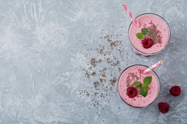 Малиновый коктейль с семенами чиа и мятой в стеклянной чашке на сером светлом каменном или бетонном столе. здоровый и вкусный завтрак. выборочный фокус.