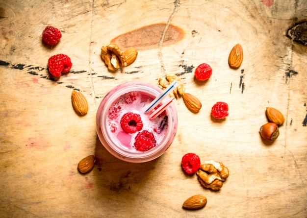 Raspberry smoothie with nuts. on wooden background.