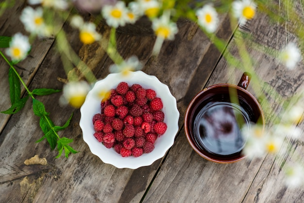Raspberry on the table with flowers. wooden background.