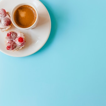 Raspberry tart with cream and coffee cup on plate over the blue background