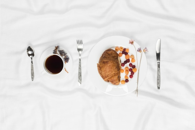 Raspberry with croissant; coffee cup with fork and spoon on white textured background