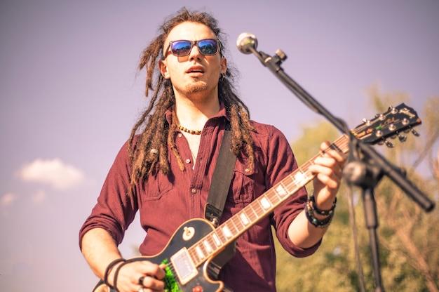 Rasta 기타리스트는 야외 콘서트에서 기타를 연주합니다.