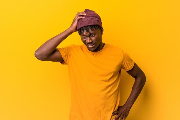 黄色の上にrastasを着た若い黒人男性は、彼は重要な会議を思い出した、ショックを受けされています。