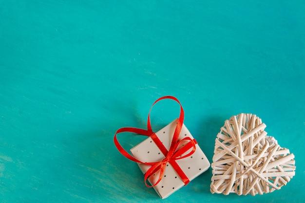 描かれたターコイズブルーの背景に赤いリボン弓で結ばれたrat編まれた白い装飾的な心エレガントなギフト弓バレンタイン