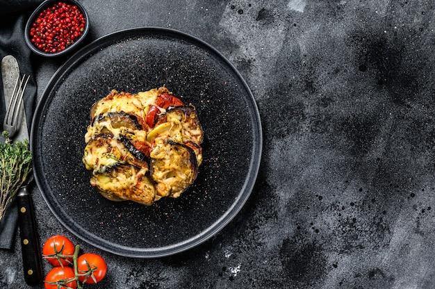 Рататуй, домашнее овощное блюдо на тарелке. вегетарианская пища. черный фон. вид сверху.