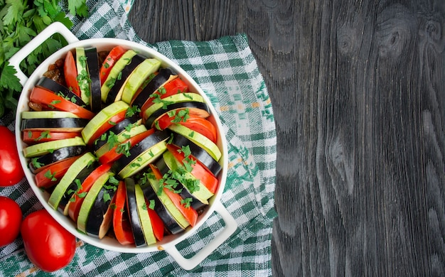 暗い木製の背景にラタトゥイユ。伝統的なフランスの野菜料理。オーブンで焼いた野菜。調理。ベジタリアンフード。スペースをコピーします。