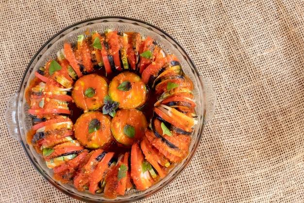 Рататуй с ломтиками помидоров, кабачками и луком. вид сверху