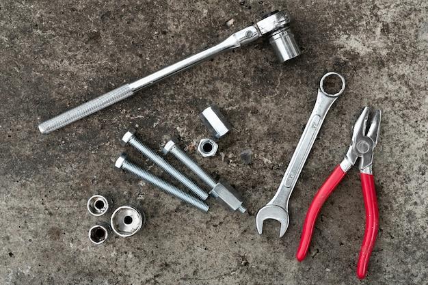 콘크리트 배경에 래치 렌치, 플라이어, 볼트 및 렌치.