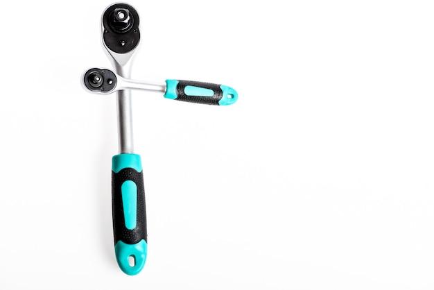 Инструмент с трещоткой. стальная ручка без скользящей ручки, которую можно удерживать, не соскальзывая. торцевые гаечные ключи на белом фоне. ручка храповика для гаечного ключа крупным планом. ключ с храповым механизмом.