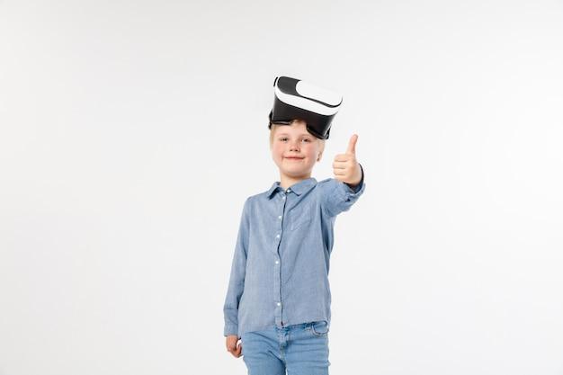 기회를 평가하십시오. 흰색 스튜디오 배경에 고립 된 가상 현실 헤드셋 안경 청바지와 셔츠에 어린 소녀 또는 아이. 최첨단 기술, 비디오 게임, 혁신의 개념.