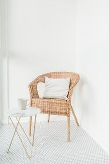 モザイクの床が付いているバルコニーの枕および大理石のコーヒーテーブルが付いている籐の椅子