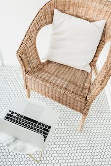 모자이크 바닥이있는 발코니에 베개와 대리석 커피 테이블이있는 등나무 의자