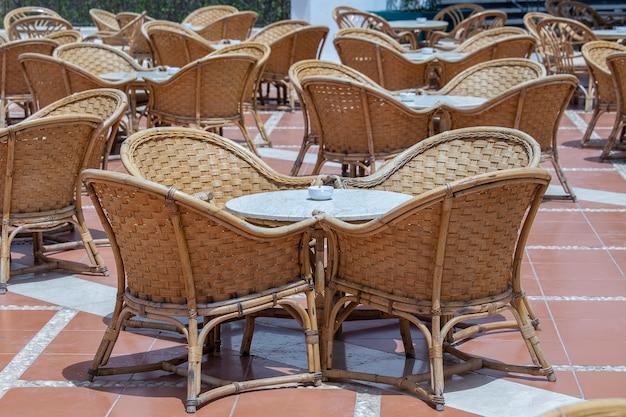 이집트 샤름 엘 셰이크의 홍해 옆 해변 카페에 있는 등나무 테이블과 의자가 닫혀 있습니다.