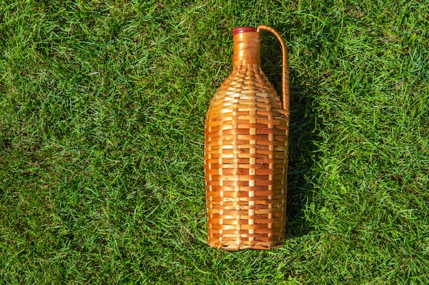 Rattan wine bottle laying on green grass lawn , pic nic concept