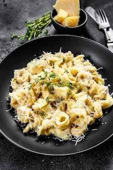 パルメザンチーズをプレートに入れたラビオリパスタ。イタリアの餃子。黒の背景。上面図。