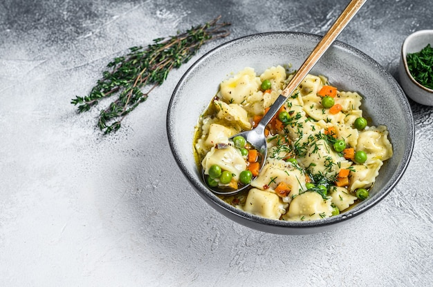 라비올리 수프 만두 채소와 함께 그릇에 파스타. 흰 바탕. 평면도. 공간을 복사하십시오.
