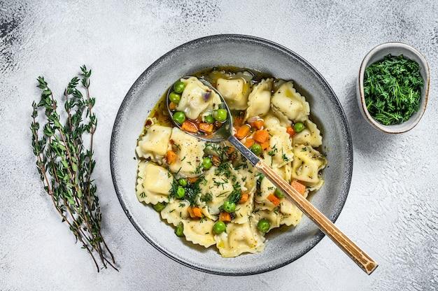 야채와 함께 그릇에 라비올리 수프 만두 파스타입니다. 흰 바탕. 평면도.