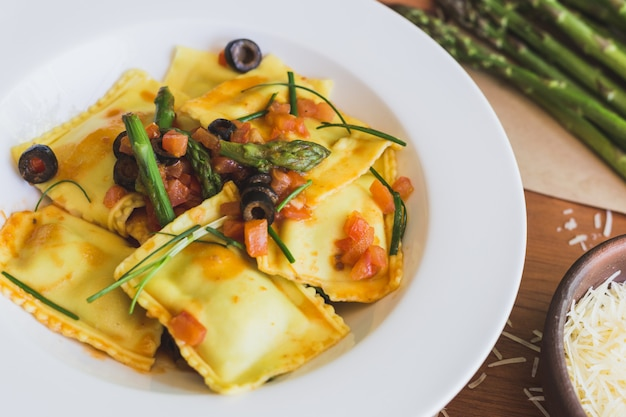 Ravioli with olives, asparagus and tomato close up