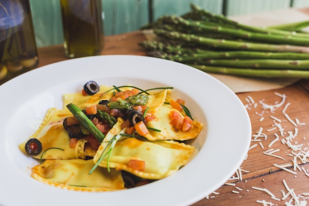 Ravioli with olives, asparagus and tomato