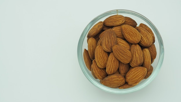 Raw almonds close up in bow and white background.