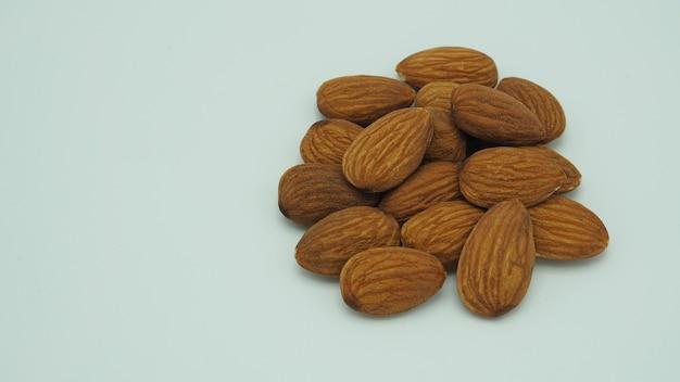 Raw almonds close up put on white background.