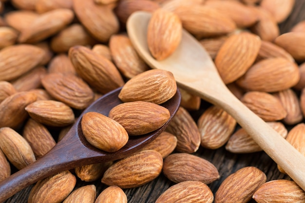 Raw almonds nut on wood spoon and wooden table.